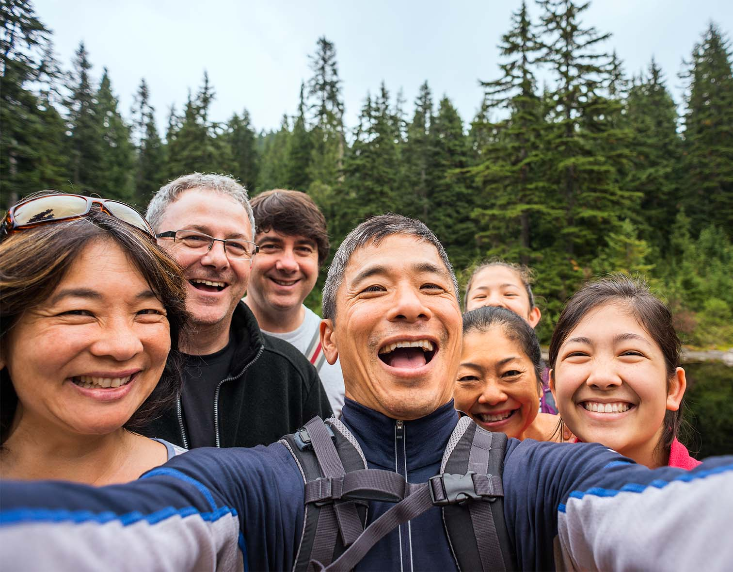 A group of related backpackers smile look at a mobile phone while taking a selfie near a lake in a wilderness park.  The group is a real multi-ethnic and multi-generation extended family of mature adults and teenage children.  Wide angle view of the forest and pond in the background.  Mount Seymour Provincial Park, North Vancouver, British Columbia, Canada.