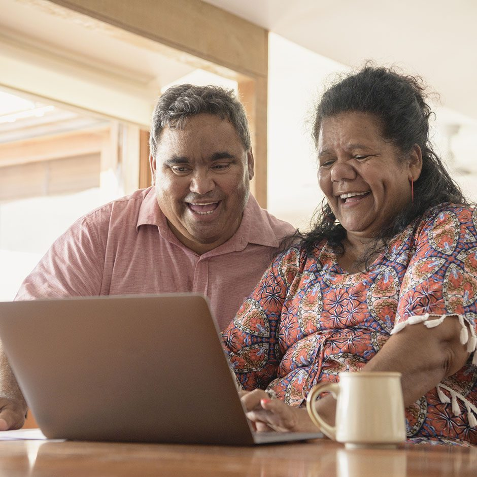 Indigenous Australian man and woman using computer and smiling side by side